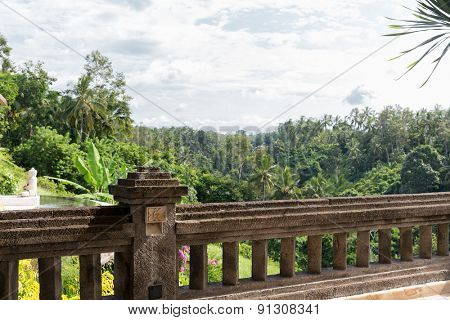 travel, touristic resort, sightseeing and tourism concept - view from balcony with stone fence to tropical woods or park at hotel or villa