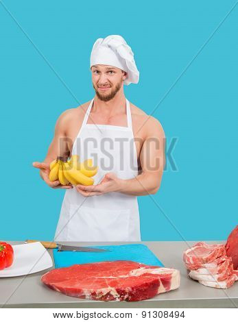 chef in a white apron holding meat and bananas