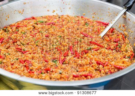 cooking, asian kitchen, sale and food concept - chilly wok or pilaf dish at street market
