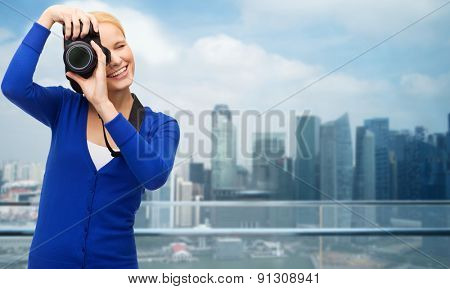 modern technology and people concept - smiling woman in casual clothes taking picture with digital camera over cityscape background