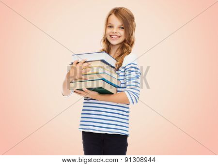education, people, children and school concept - happy little student girl with many books over beige background