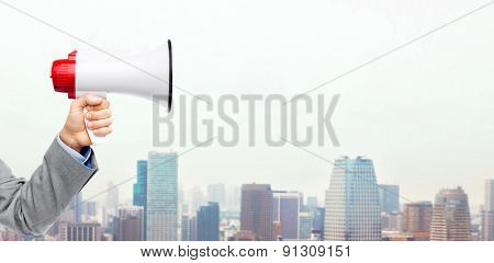 business, people and public announcement concept - close up of male hand in suit with megaphone over city background