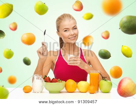 healthy eating, diet, organic food and people concept - happy woman eating yogurt and having breakfast over green background with falling fruits