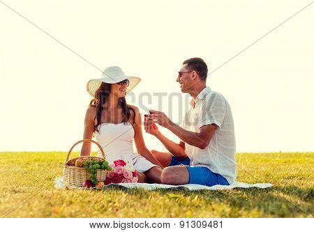 love, dating, people and holidays concept - smiling young man showing small red gift box to his girlfriend on picnic