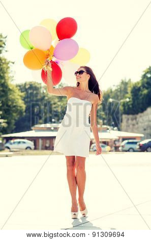 happiness, summer, holidays and people concept - smiling young woman wearing sunglasses with balloons in park