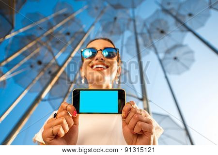 Woman holding phone standing on the abstract background
