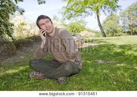 young man sitting and talk on mobile phone, against green of summer park.