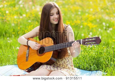 Young woman playing an acoustic guitar outdoors