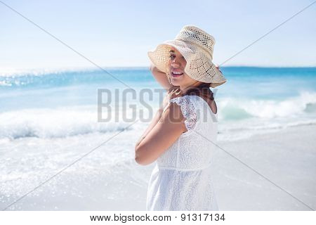 Pretty brunette wearing straw hat and looking at camera at the beach