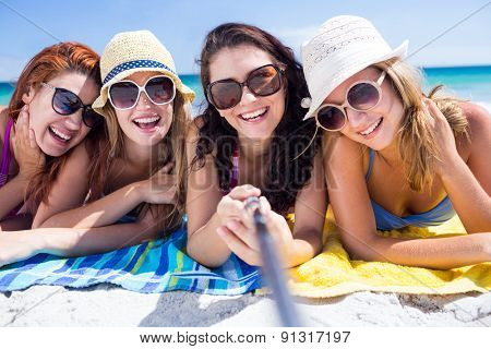 Happy friends wearing sun glasses and taking selfie at the beach