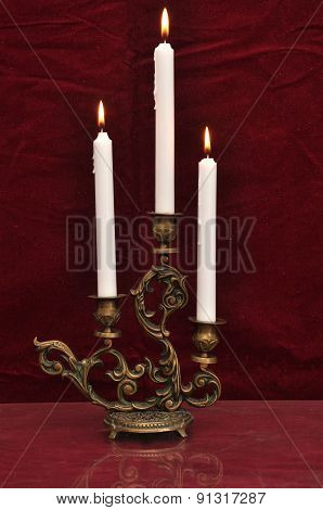 Antique Candelabra With Three Melting Candles On A Dark Red Velvet Background
