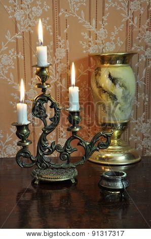 Antique Candelabra With Three Melting Candles On An Old Wallpaper Background