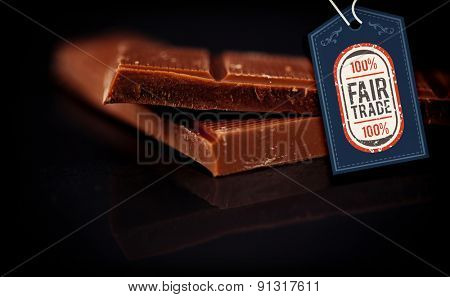 Fair Trade graphic against two blurred bar of dark chocolate