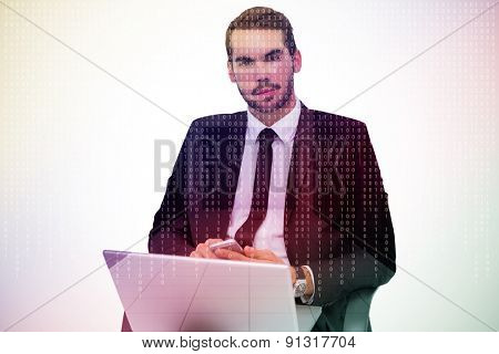 Cheerful businessman with laptop using smartphone against server room with towers