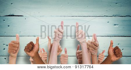 Hands showing thumbs up against painted blue wooden planks