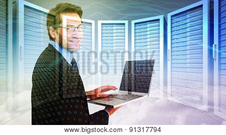 Smiling businessman using a laptop against server room