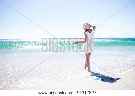 Pretty brunette wearing straw hat and walking in the water at the beach