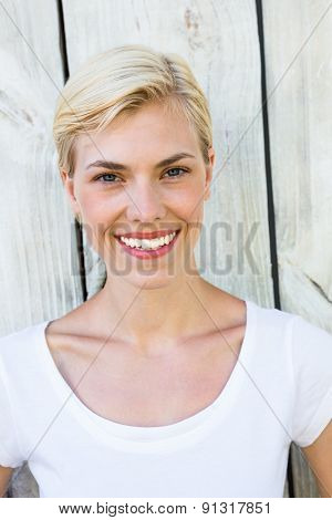 Attractive blonde woman looking at camera on wooden background