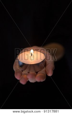 Hand holding candle on black background