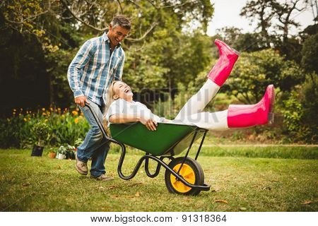 Happy couple playing with a wheelbarrow on a sunny day