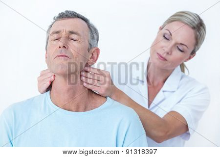 Doctor stretching her patient neck in medical office
