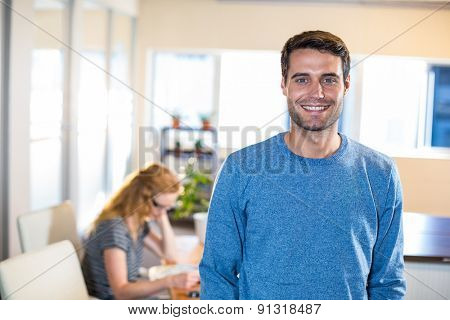 Smiling casual businessman posing with his partner behind in the office