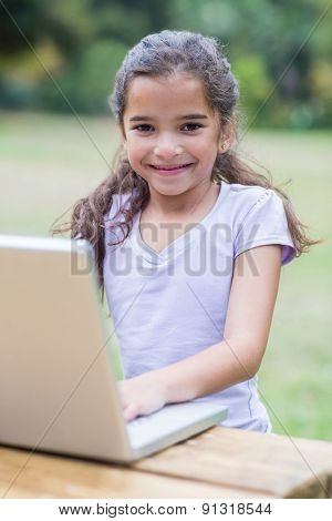 Little girl using her laptop in a park on a sunny day