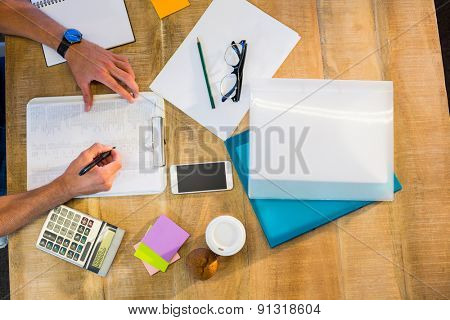Man writing on clipboard on working desk