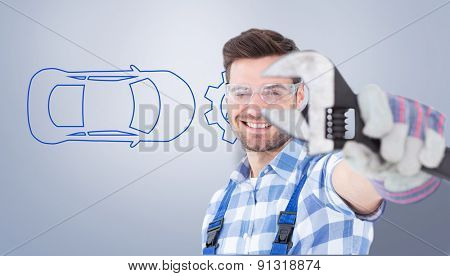Handyman wearing protective glasses while holding wrench against grey vignette