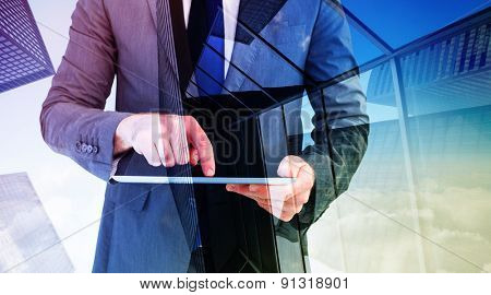 Businessman using his tablet pc against skyscraper