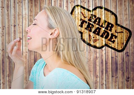 Pretty blonde eating a chocolate against wooden planks