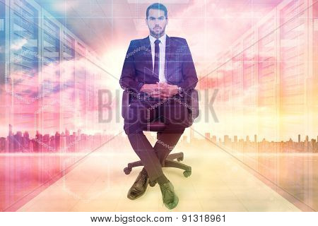 Stern businessman sitting on an office chair against server room with towers