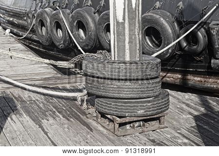 A barge with a series of tires along its hull for use as bumpers when interacting with other vessels.