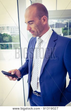 Businessman sending a text message in his office