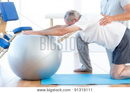 Physiotherapist helping man with exercise ball in medical office