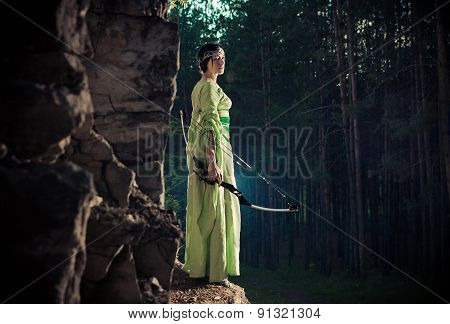 Elf Woman With The Magic Bow On The Forest Background.