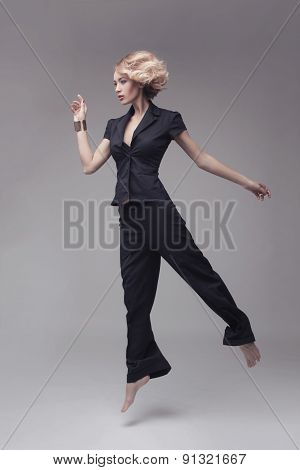 Fashion photo of  jumping woman in black suit