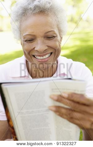 Senior African American Woman Reading Magazine In Park