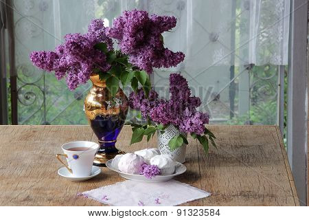 Tea In A Porcelain Cup, A Zephyr And A Lilac Bouquet In A Beautiful Vase