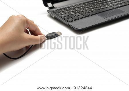 Hand Holding Usb Cable And Laptop