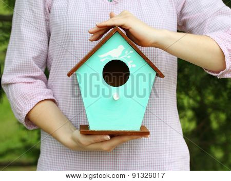 Decorative nesting box in female hands on bright background
