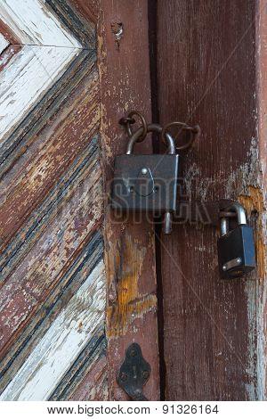 Two Padlocks On Old Wooden Door