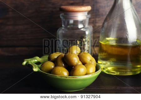 Olives With oil on table on wooden background