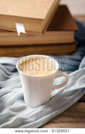Still life with cup of coffee and books, on wooden table