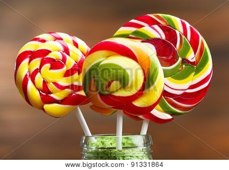 Colorful candies in jar on table on wooden background