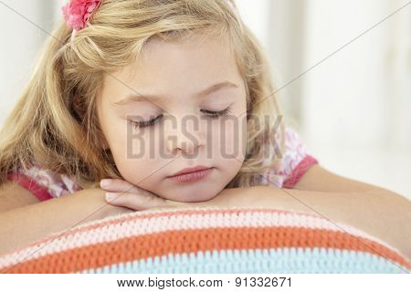 Young Girl Relaxing On Cushion On Floor In Bedroom