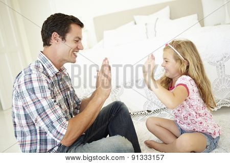 Father And Daughter Playing Together In Bedroom