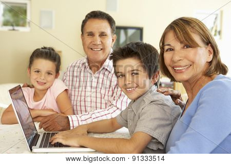 Hispanic Grandparents And Grandchildren Using Computer At Home