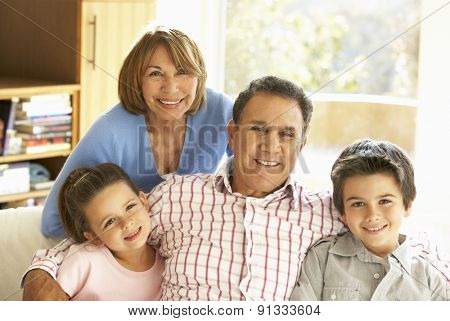 Hispanic Grandparents With Grandchildren Relaxing On Sofa At Hom