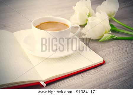 Beautiful tulips with book and cup of coffee on wooden background